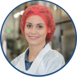 Female Line Operator with red hair net optimizing equipment effectiveness