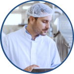 Male Production Line Supervisor with white hair net viewing real time data from their OEE software solution